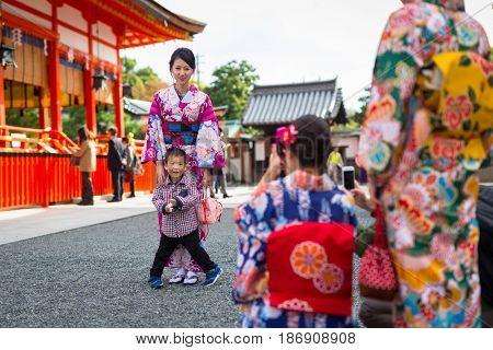 KYOTO, JAPAN - NOVEMBER 10, 2016: Young women wearing traditional japanese kimonos at Fushimi Inari Shrine in Kyoto, Japan. Kimono is a Japanese traditional garment.