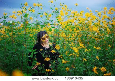 Portrait of a young girl brunette in sunglasses decorated with yellow flowers posing among dense Jerusalem artichokes in a Sunny summer day during a country walk