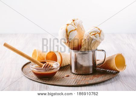 Waffle cone with ball of vanilla ice cream with caramel in a metal glass on a table