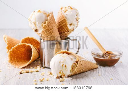 Waffle cone with ball of vanilla ice cream with nuts in a metal glass on a table