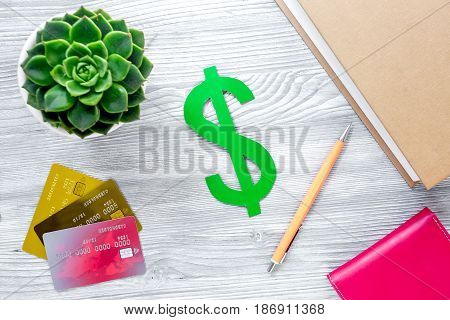 paying for studing concept with dollar sign and credit cards on light table background top view