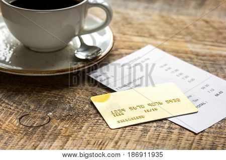 cup of coffee and receipt bill for payment by credit card on wooden table background
