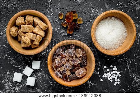 sugar in lumps for sweet food cooking on kitchen dark table background top view