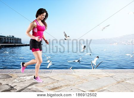 Athletic woman runner in sportswear on the sidewalk near the sea
