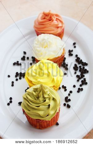 Colorful Cupcake  With Chocolate On White Platter