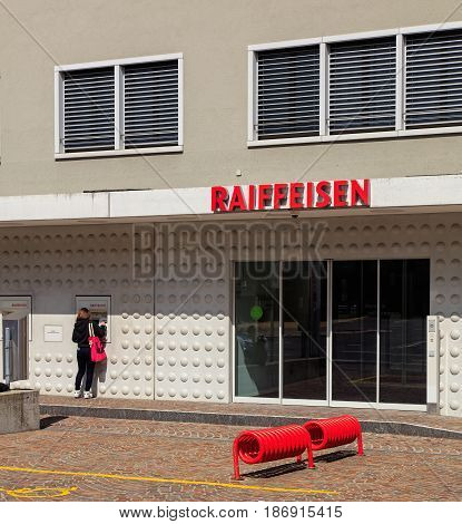 Einsiedeln, Switzerland - 7 September, 2015: entrance to an office of the Raiffeisen bank, a person at the ATM. Raiffeisen is a Swiss cooperative bank, it is the third largest bank in Switzerland, after UBS and Credit Suisse.
