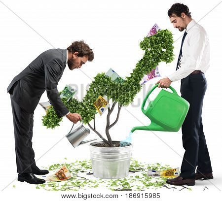 Businessmen watering money coins as if they were plants