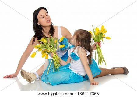 Beautiful young mother and little daughter in the same blue long skirts tutus , standing sideways to the camera , admiring the bouquet of yellow tulips.Isolated on white background.