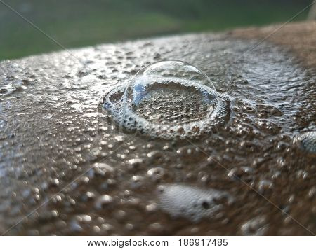 large soap bubble on a wood deck railing