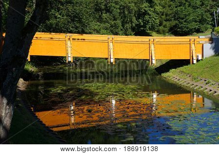 Foot-path bridge and its reflection in water. Palanga, Lithuania.