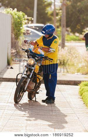 Cabedelo Paraiba Brazil - May 17 2017 - Postman of Empresa Brasileira de Correios e Telegrafos (English: Brazilian Post and Telegraph Corporation)also known as Correios delivering correspondence on motorcycle