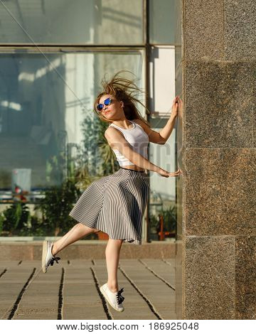 Young attractive hipster girl dancing outdoors. She is dressed in a top skirt and sunglasses. Flying hair. The concept of life in motion.