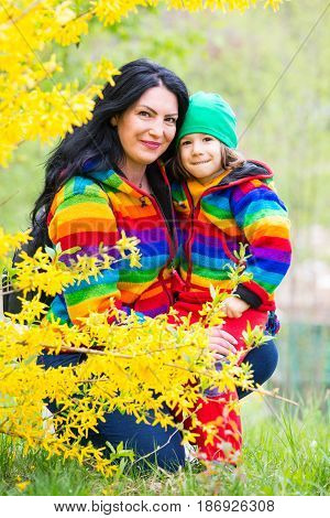 Happy mother and son in rainbow hoodies having fun in park
