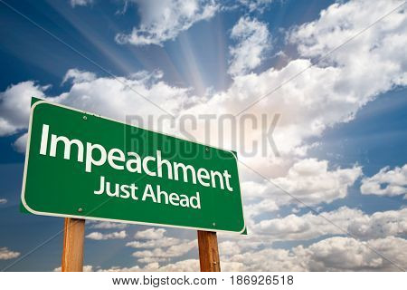 Impeachment Green Road Sign with Dramatic Clouds and Sky