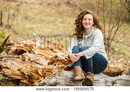Happy curly hair woman sitting on trunk tree in nature