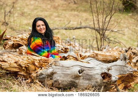 Happy woman in rainbow hoodie sitting on bark tree in nature
