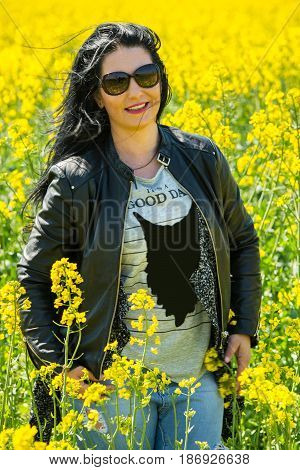 Attractive brunette woman posing in rape field in sunny day