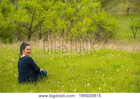 Smiling woman take a rest and sitting on spring grass with dandelions