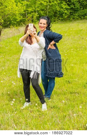 Friends women making selfie with their smartphone in nature
