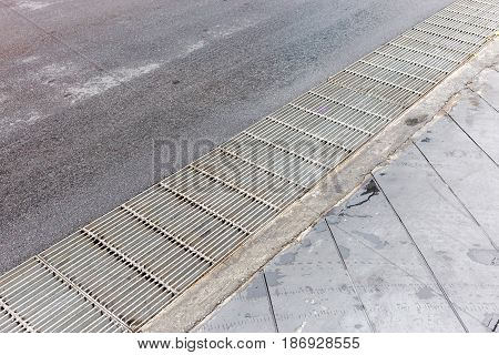 Steel grate drainage (manhole) along to the street in downtown city.