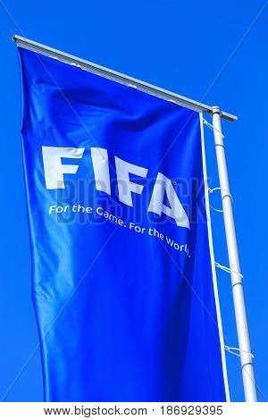 Zurich, Switzerland - 11 April, 2016: one of the flags at the entrance to the FIFA headquarters against blue sky. FIFA is the international governing body of association football and beach soccer, headquartered in the city of Zurich.