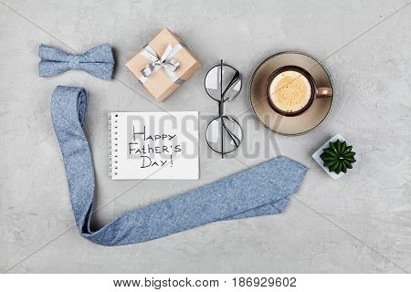 Happy Fathers Day background with morning coffee mug gift glasses necktie and bowtie on stone table top view in flat lay style.