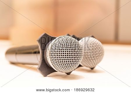 Two microphones with warm fall color and blurred focus meeting room in background.