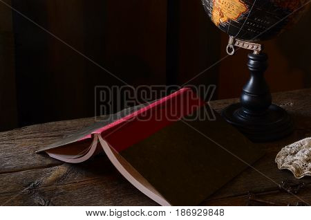 A dark and moody image of an upside down book on an old wooden desk.