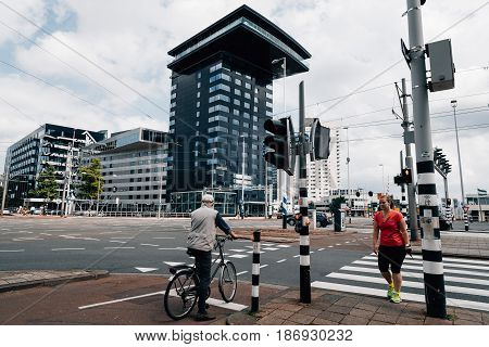Rottedam The Netherlands - August 6 2016: People crossing the street. Rotterdam is home to some world famous architecture from renowned architects