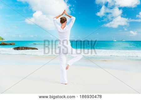Photo of a young woman practicing yoga on the beach