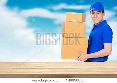 Wood table top on blue sky and deliveryman background - can be used for display or montage your products