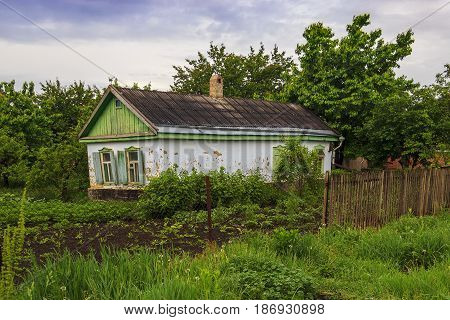 The old house built of clay around it a kitchen garden and trees. The house one-storey outside of white color.
