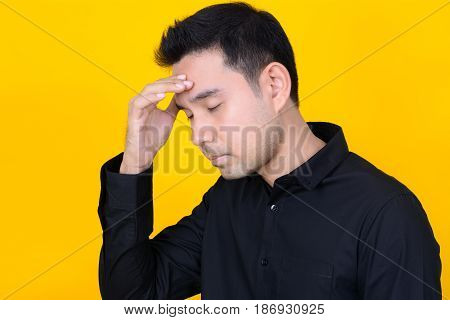 Young Asian man with hand on temple - tired stress and headache concepts