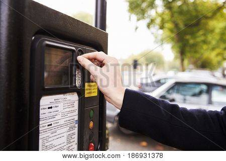 Close Up Of Man Putting Money In Parking Meter For Ticket