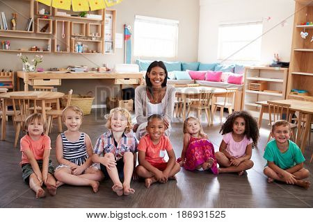 Portrait Of Teacher With Pupils In Montessori School Classroom