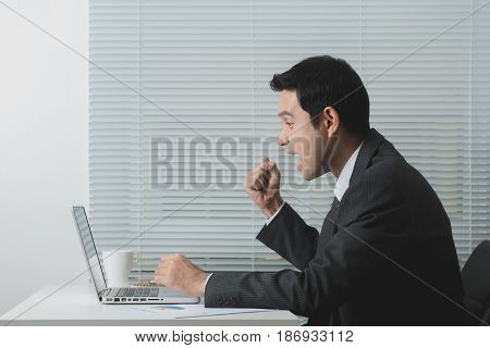 Businessman looking at laptop computer and raising his fist with delighted feeling in the office soft tone