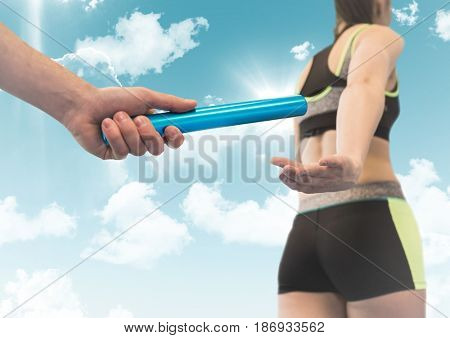 Digital composite of Relay runner and hand with blue baton against sky with flares