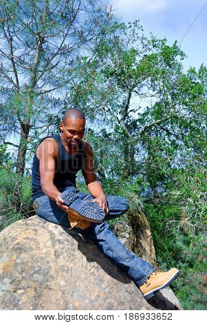 Young black male hiker adjusting his hiking boot while sitting on top of a rock