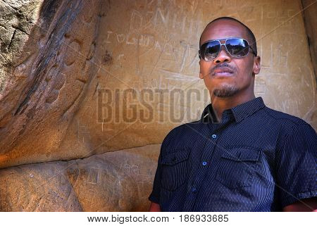 Portrait of a young black man wearing sunglasses at the entrance to a cave