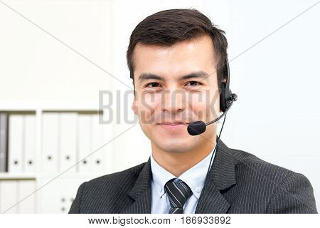Smiling handsome businessman wearing microphone headset - telemarketing operator call center and customer service concepts