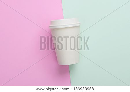 Disposable takeaway (take out) coffee cup on light blue and pink background