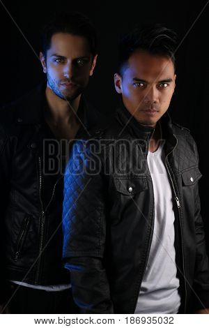 two attractive vampires posing on a black background