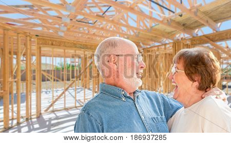 Senior Couple On Site Inside Their New Home Construction Framing.