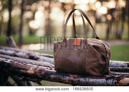 Travel backpack on the wooden bench in the forest. Summer active hiking and trekking tools