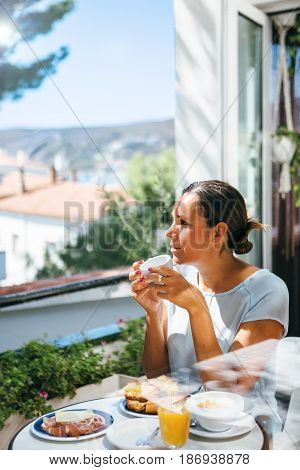 Vertical outdoors shot of adult pretty woman having hot beverage during the breakfast.