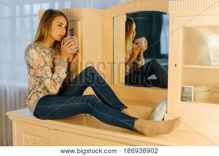 The pensive teenage girl is holding the cup of tea while sitting on the dressing-table