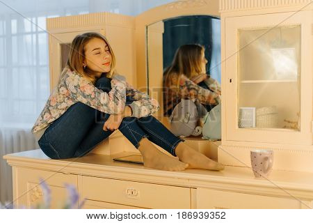 The horizontal close-up photo of the dreaming young teenager hugging her knees while sitting on the dressing-table