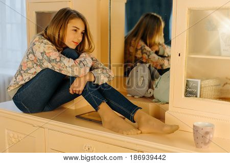 The close-up view of the smiling teenage girl hugging the knees and sitting on the dresser