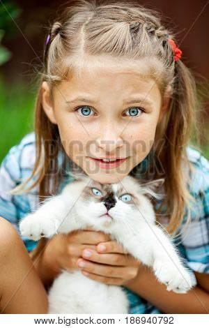 Young beautiful girl with freckles and with a scared kitten in his hands in the park