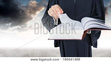Digital composite of Judge holding book in front of sky clouds